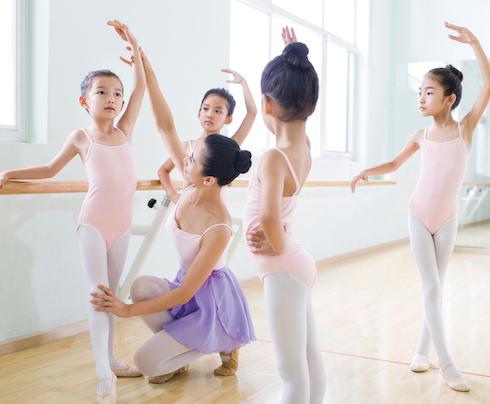 Young Chinese ballet instructor teaching girls in ballet studio